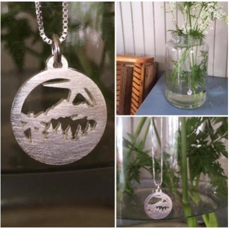Halsband i silver med ett hänge föreställande en vy över skog, sjö, fjäll