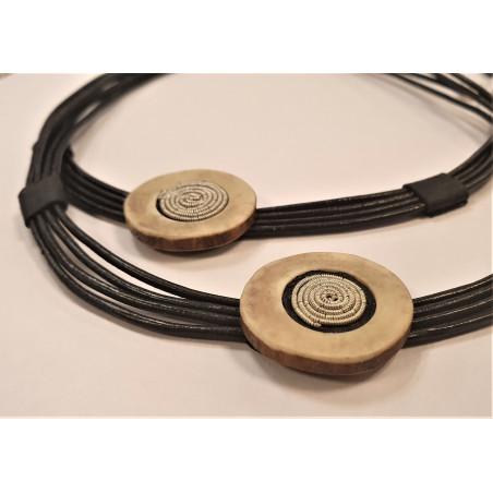 Halsband i svart läder med en detalj i horn broderad med tenntråd
