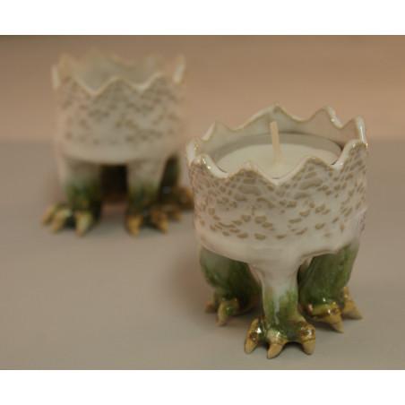 Gröna odjursfötter på en vit spetsliknade krage, keramik